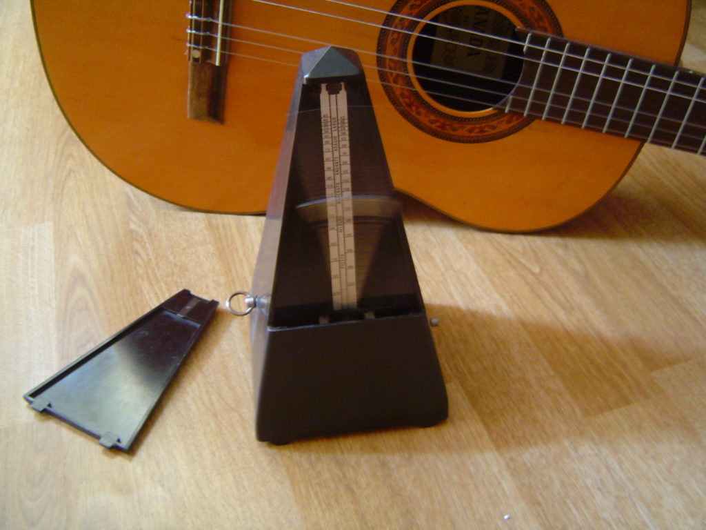 Acoustic guitar and metronome. A metronome is commonly used in the recording studio.