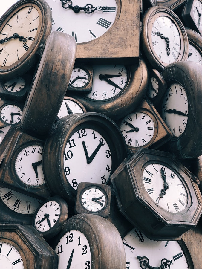 a pile of wooden wall clocks