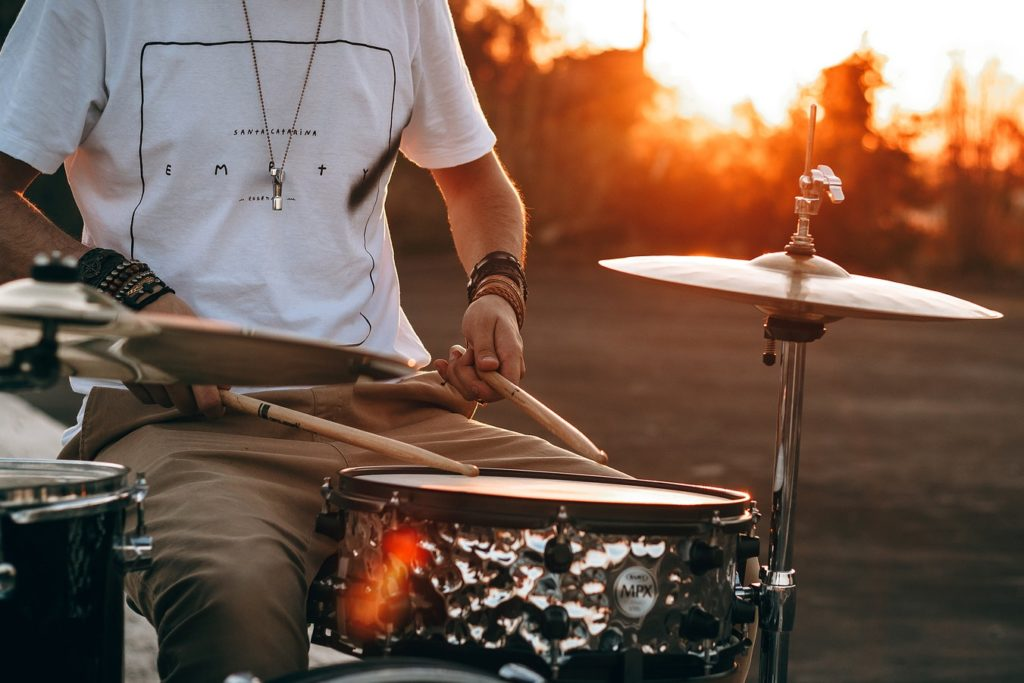 man practicing drums outside