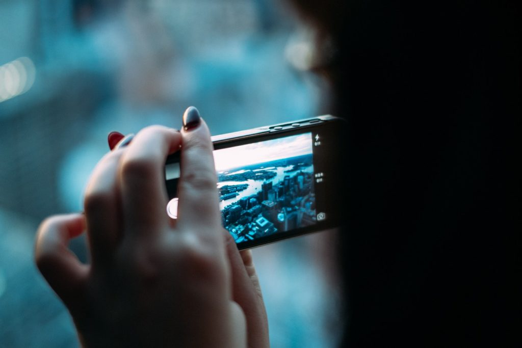 woman holding smartphone taking a video of a city