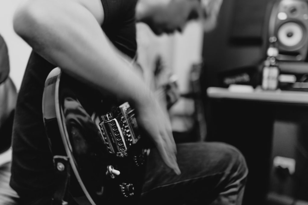 black and white photo of a guitarist in a home studio