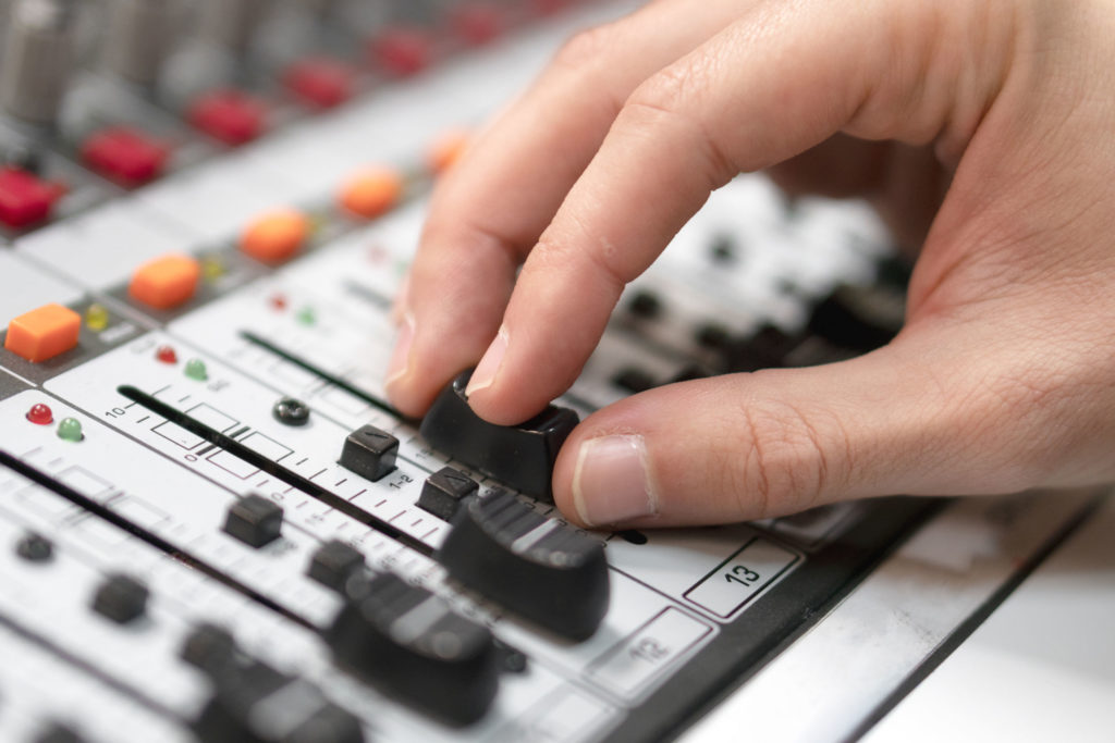 hand moving fader on mixing console in music production school